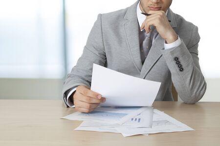 documentos: Hombre de negocios sentado mesa y sosteniendo documento