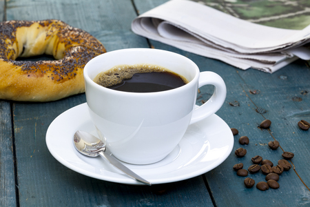 bagel: Cup of coffee with bagel and newspaper