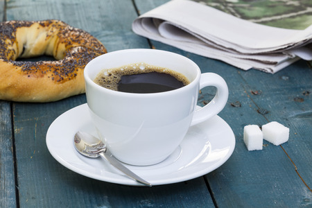 Cup of coffee with bagel and newspaper