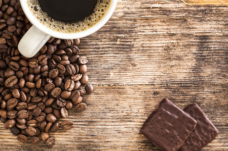 coffee beans: Coffee cup and chocolates on a wooden table