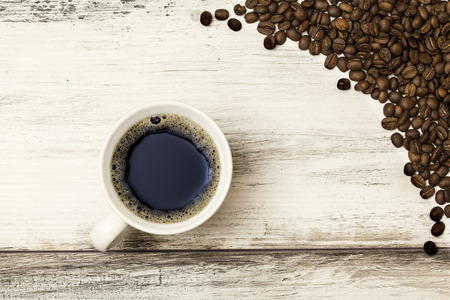 up view: Coffee cup and beans on a wooden table