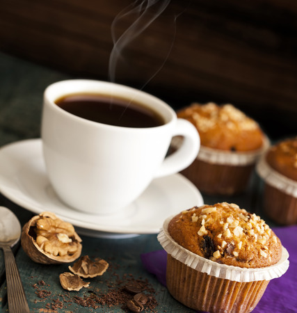 Muffin cakes in silver tray with cup of coffee Фото со стока