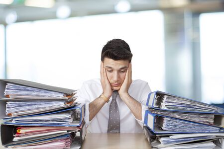 business help: Bored businessman in office with files Stock Photo
