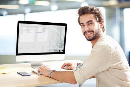 コンピューターに取り組んでいる若い男 写真素材