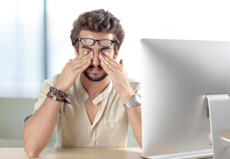 man working on computer: Young man with eyes pain touching his eyes