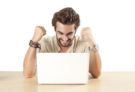 Young man with raised fists using laptop