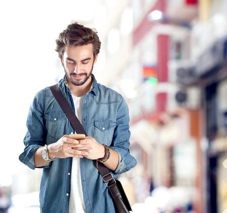 jovenes felices: Hombre joven que usa el teléfono móvil en la calle
