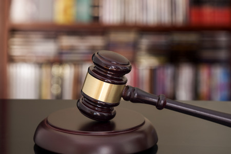 court judge: Wooden gavel on library background