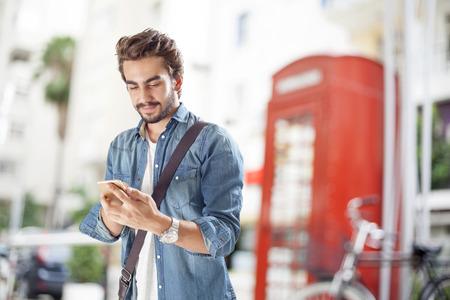 hombre escribiendo: Hombre joven que usa el teléfono móvil en la calle