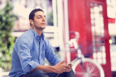 personas escuchando: El hombre escuchando música con teléfono móvil