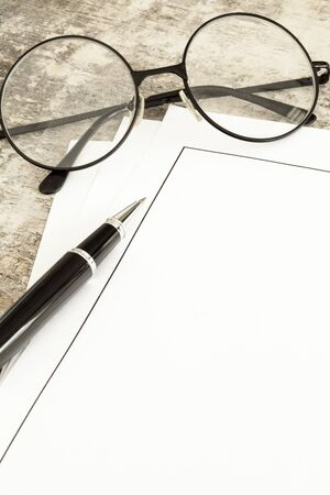 carta e penna: Blank paper, pen and glasses on wooden table
