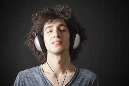 헤드폰 젊은 남자가 음악을 듣고 스톡 콘텐츠