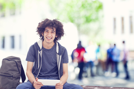 young man smiling: Young man holding digital tablet Stock Photo
