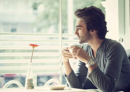 Young man drinking coffee in cafe