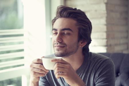 カフェでコーヒーを飲みながら若い男