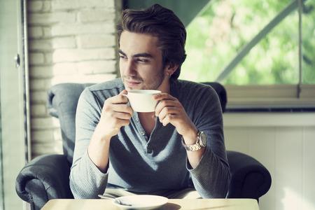 hombre tomando cafe: Joven beber café en café