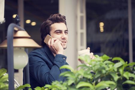hablando por telefono: El hombre joven teléfono hablando en café