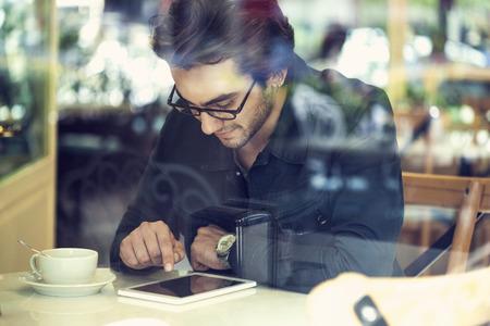 Giovane uomo con tavoletta digitale in un caffè