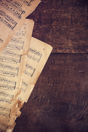 paper old: Music sheets on wooden background Stock Photo