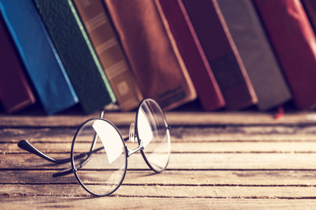 hardback: Old hardback books and eyeglasses