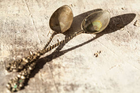 tarnished: Old spoon on wooden table Stock Photo