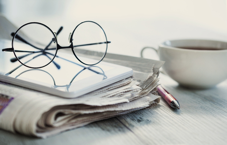Stack of newspapers, eyeglasses on table Archivio Fotografico