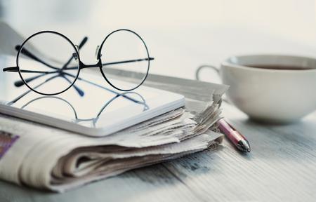 Stack of newspapers, eyeglasses on table Standard-Bild