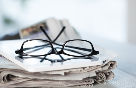 Stack of newspapers, eyeglasses and digital tablet Stock Photo