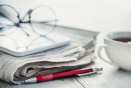 Stack of newspapers, eyeglasses on table Foto de archivo