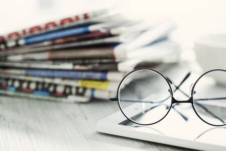 read news: Stack of newspapers, eyeglasses and digital tablet Stock Photo