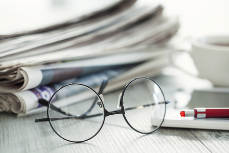 coffee table: Stack of newspapers, eyeglasses and digital tablet Stock Photo