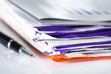 stack of papers: Stack of bills and pen