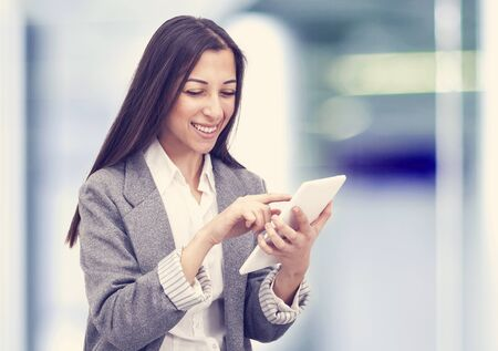 wireless woman work working: Smiling business woman holding a tablet computer at the office Stock Photo