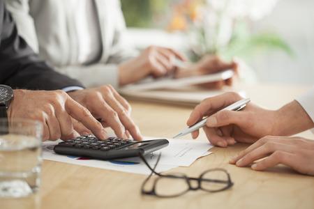 calculadora: La gente de negocios que trabajan en la oficina Foto de archivo