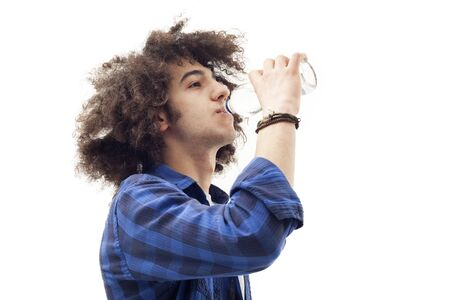 man drinking water: Young man drinking water from glass bottle Stock Photo