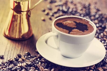 greek pot: Cup of coffee on wooden table Archivio Fotografico