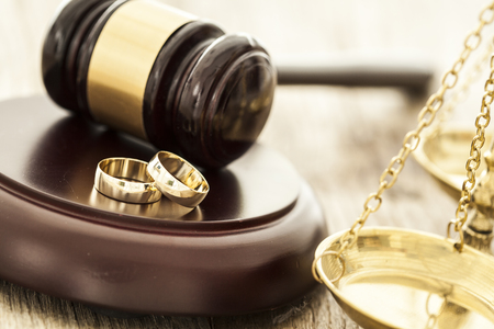court: Divorce concept with gavel and wedding rings