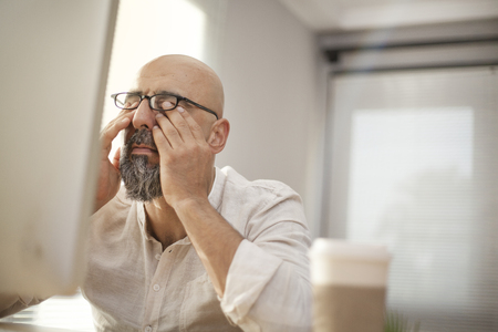 Senior businessman rubbing his tired eyes Stock Photo