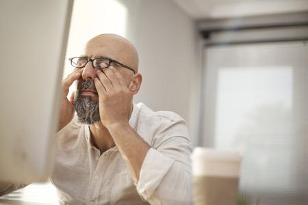 Uomo d'affari maggiore stropicciandosi gli occhi stanchi