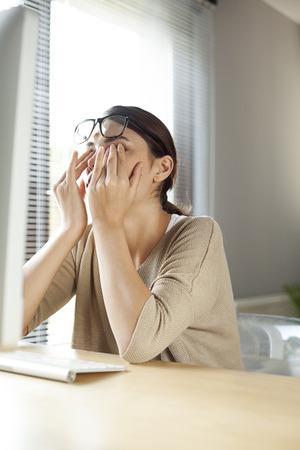 Businesswoman rubbing her tired eyes