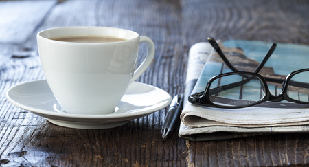 Stack of newspapers with coffee