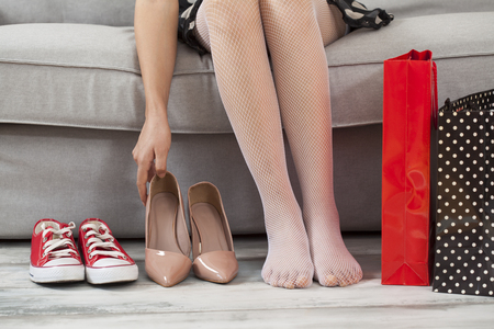 shoes woman: Young woman sitting sofa with shoes