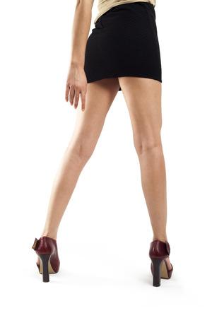 piernas mujer: Piernas de la mujer que desgastan los altos talones sobre el fondo blanco