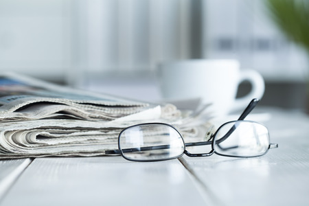 Stack of newspapers and eyeglasses Foto de archivo