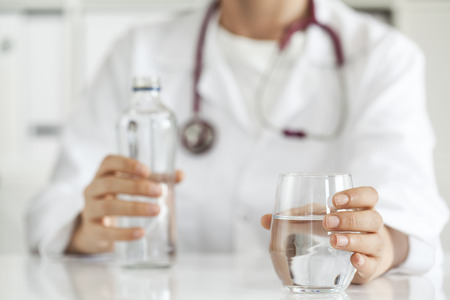 agua potable: Doctor de la mujer con el agua potable
