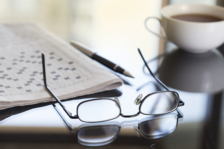crosswords: Newspaper glasses and coffee Stock Photo