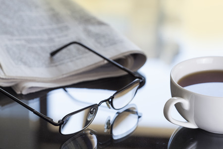 Newspaper glasses and coffee Stock Photo