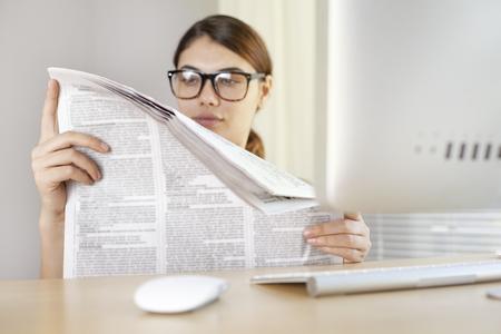 broadsheet: Young woman reading newspaper