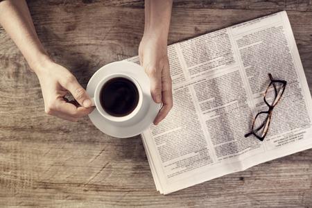 periodicos: periódico de la lectura de la mujer joven y la celebración de la taza de café