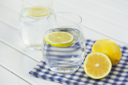 Glass of water with lemon on white background Stockfoto